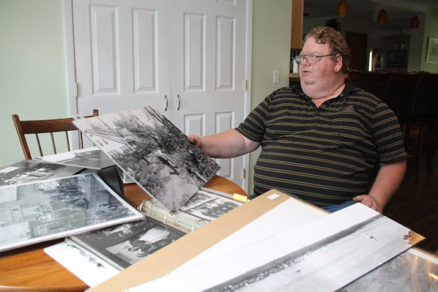 Mike Richter displays a photo taken by Hugo Frey that shows damage caused by the 1938 hurricane. It's one of thousands in his collection of historical photographs of local subjects. (Credit: Paul Squire)