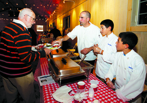 Hellenic Snack Bar manager George Giannaris and sons Yianni (center) and Savvas serve chili to John Rooney of Southold at North Fork Environmental Council's Chili Night last year.