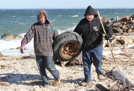 Thirteen-year-olds Connor Whittle, left, and Nicky Mackey remove a discarded tire from the beach.