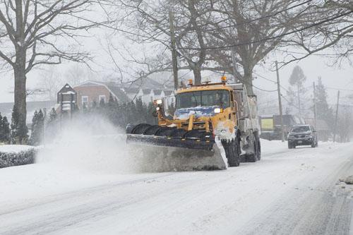 KATHARINE SCHROEDER PHOTO | A snow plow clears the road near Mattituck.