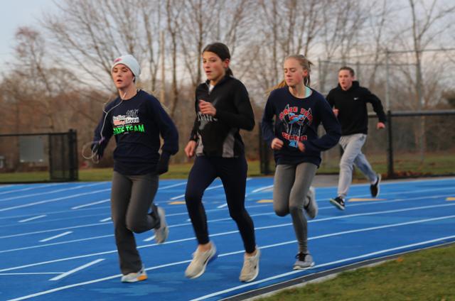 Mattituck's Melanie Pfennig, left, Payton Maddaloni and Kylie Conroy run at practice Tuesday. (Credit: Joe Werkmeister)