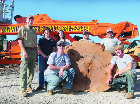 Back row, from left: Owner Kevin Carrick, office manager Karen Carrick, staff member Danielle Carrick and employees Thomas Canel and Emilio Canel. Kneeling: brothers Joshua (left) and Brian Carrick.