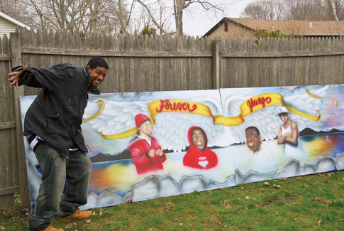John R. Mims Jr. with the mural he created for Saturday's Global Youth Services Day cleanup at the Third Street basketball courts in Greenport. The mural honors four Greenport youths, Michael Brown, Corey Freeman, Kyle Rose and Naquawn Treadwell, who died in accidents in recent years. Members of Youth Engaged in Service also spruced up the park and painted and planted flower boxes.
