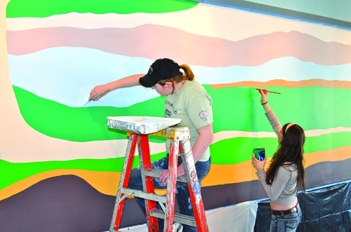 Lauryn Serrano (left) and Mackenzie Robertson were two of six Mattituck High School art students who helped create a mural in the new community room at Veterans Memorial Park in Mattituck. Fellow students Morgan Gildersleeve, Brigid Bozsnyak, Nicole Palladino and Emily Fliss also worked on the abstract painting in a cooperative program between the school and Mattituck Park District.