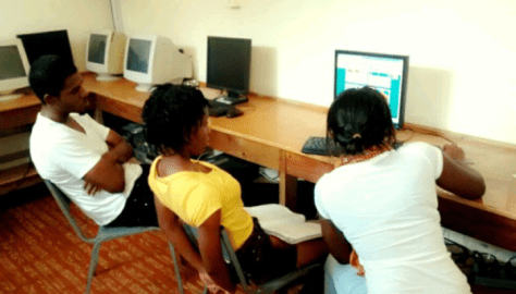 Rotaractors Marvin and Patrice of the Rotaract Club of Kingston assist a child at their Homework Programme at the Shelly-Ann Fraser-Pryce Centre on Saturday, January 17, 2015