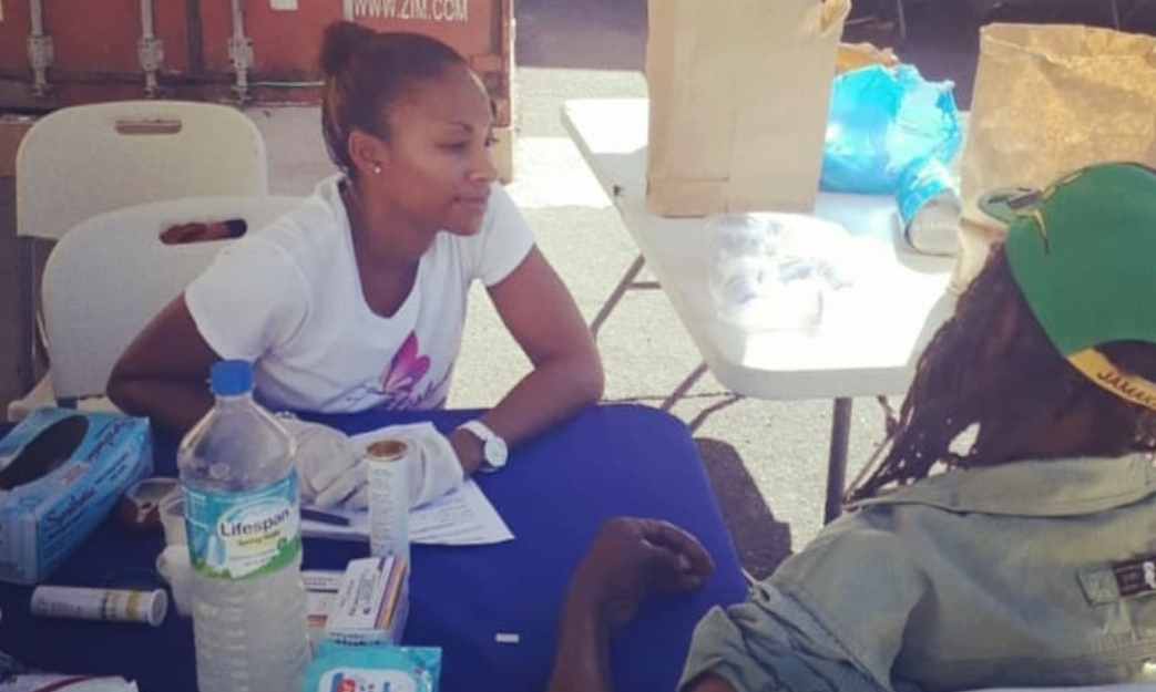 Gabrielle Burgess, founder and owner of Suga Lifestyle assisting with medical checks at the Rotaract Club of New Kingston's Marie Atkins Shelter Health Fair and Feeding project of which she helped to sponsor. [Saturday, January 20, 2019]