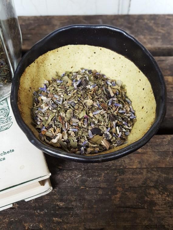 Sugar and Pith Courtesan's Choice herbal bath soak, close up shot of loose herbs in a rustic ceramic bowl