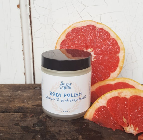 Sugar and Pith ginger and pink grapefruit body polish, single jar surrounded by wedges of pink grapefruits