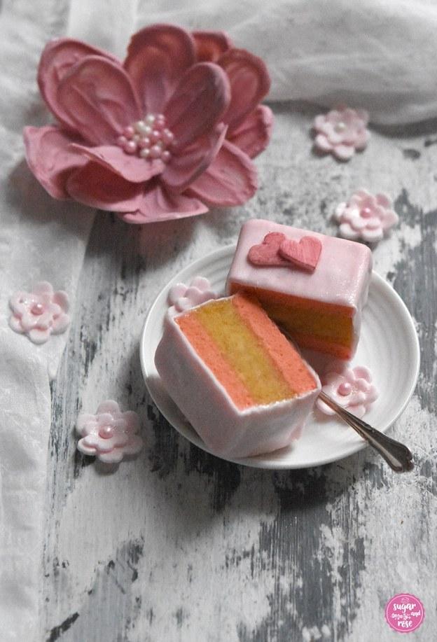 Eierlikör-Punschkrapferl aufgeschnitten mit rosa Schokoladenblüte