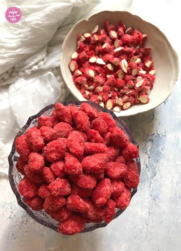 Pralines Roses in Glasschale und gehakte rosa Mandeln in weißer Keramikschale