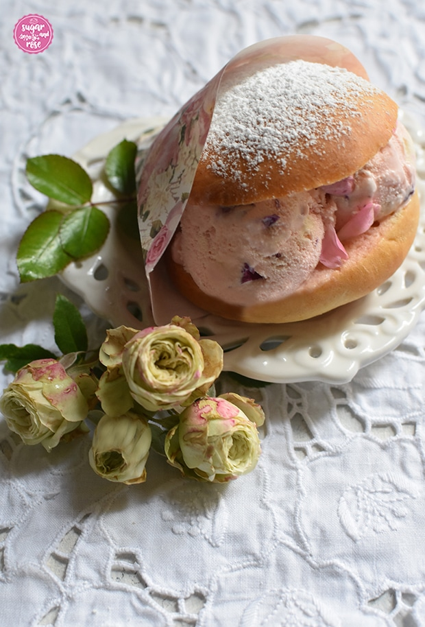 Eisburger (Brioche con Gelato) in Papiertüte mit Rosenmotiv, gefüllt mit Roseneiskugeln, daneben kleine grüne Rosen