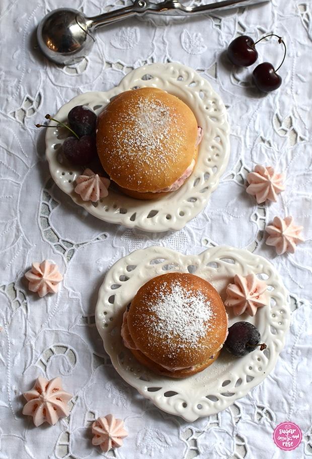 Zwei Eisburger (Brioche con Gelato) auf jeweils einem herzförmigen Keramikteller mit Lochmusterdekor auf einem weißen Platzset mit Lochstickerei, dekoriert mit Kirschen und rosa Baisertuffs, dahinter als Deko ein leerer Eisportionierer aus Stahl