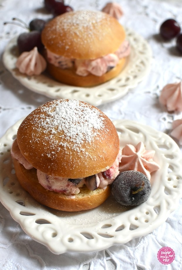 Zwei Eisburger (Brioche con Gelato) auf jeweils einem herzförmigen Keramikteller, gefüllt mit Kirscheneis. Der vordere Eisburger in Nahaufnahme, dekoriert mit gefrorenen Kirschen und rosa Baisertuffs