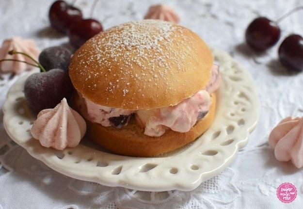 Ein mit Puderzucker bestäubter Eisburger (Brioche con Gelato) auf einem herzförmigen Keramikteller, gefüllt mit rosa-weiß marmoriertem Kirscheneis, dekoriert mit Kirschen und rosa Baisertuffs