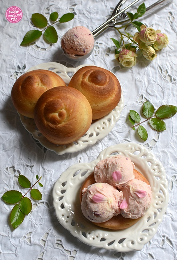 Drei rosa Roseneiskugeln auf einem aufgeschnittenen Brioche, liegend auf einem herzförmigen weißen Vintage-Keramikteller, dahinter ein weiterer Keramikteller mit drei ungefüllte Briocheweckerln von oben und ein Eisportionierer mit einer Kugel Roseneis. Als Deko ein Zweig mit grün-rosa Röschen der Rose Lovely Green