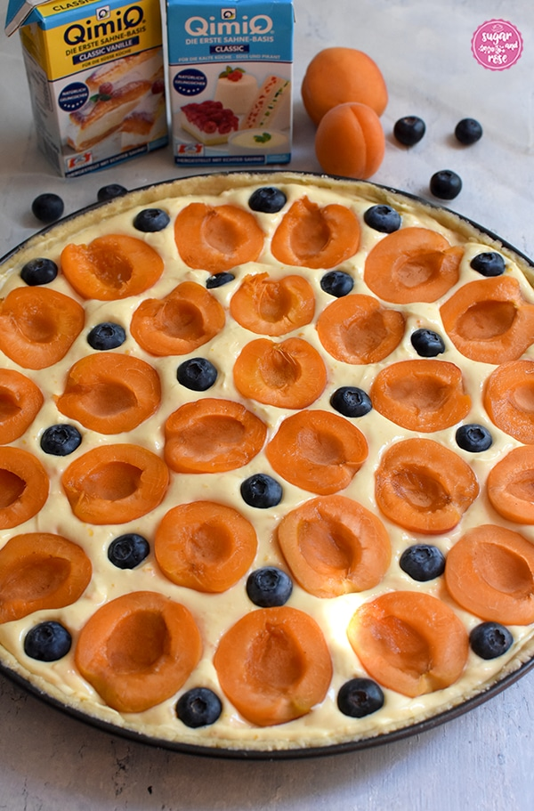 Runde Tarteform mit Marillen-Tarte vor dem Backen. Halbierte Marillen und Heidelbeeren ruhen im Topfenbeet. Hinter der Tarteform stehen zwei Packungen Qimiq