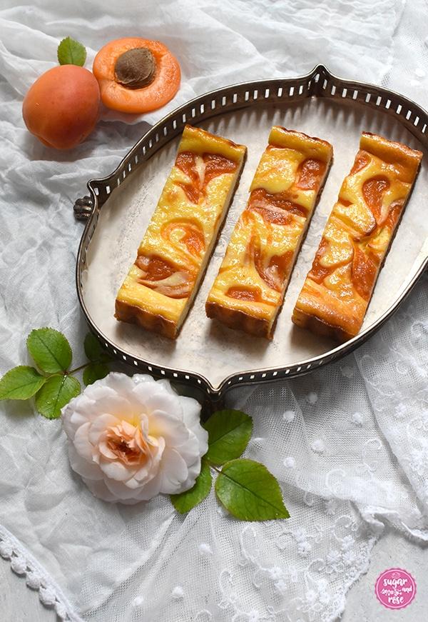 Marillen-Ricotta-Tarte aufgeschnitten auf flachem silbernen Jugendstiltablet mit Rand, dekoriert mit einer milchigweißen Rosenblüte und zwei Marillen