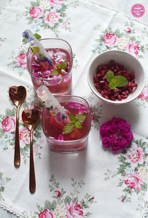 Rosé-Gin-Cocktail mit Granatapfelkernen in zwei eckigen Whiskeygläsern, daneben zwei rosegoldfarbene, herzförmigen Metalllöffelchen, eine Schale mit Granatapfelkernen und Minzblatt, alles auf einer weißen Leinenserviette mit zartrosa Rosenmotiven. In den Cocktailgläsern stecken längliche Eiswürfel mit eingefrorenen Blüten