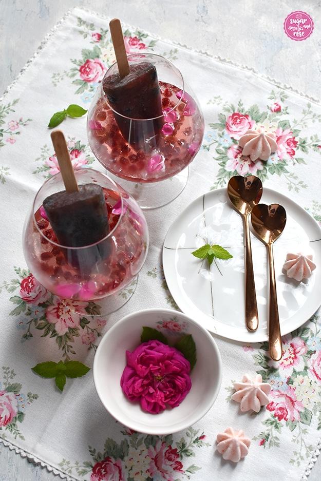 Rosé-Gin-Cocktail mit Granatapfelkernen in zwei Cognac-Schwenkern, daneben ein zarter weißer Porzellanteller mit zwei rosegoldfarbenen, herzförmigen Metalllöffelchen, eine Schale mit einer pinkfarbenen Rose und zartrosa Baisertuffs auf einer weißen Leinenserviette mit zartrosa Rosenmotiven. In den Cocktails stecken dunkelrote Eislutscher mit Stiel