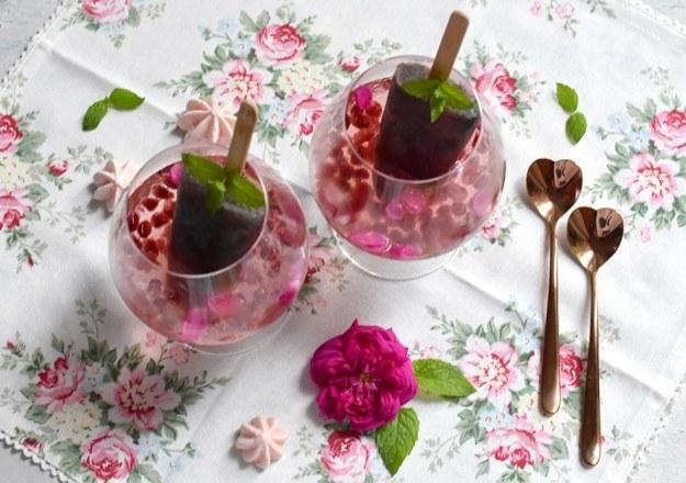 Rose Gin Cocktail in zwei Cognac-Schwenkern mit Himbeeren und Granatapfelkernen. In den Cocktails jeweils ein Rose-Gin-Eislutscher mit Minze-Deko. Daneben zwei rosegoldfarbene herzförmig Löffelchen und eine dunkelpinke Rosenblüte. Die Leinenserviette mit Rosenmotiven ist dekoriert mit blassrosa Baisertuffs und Minzblättern