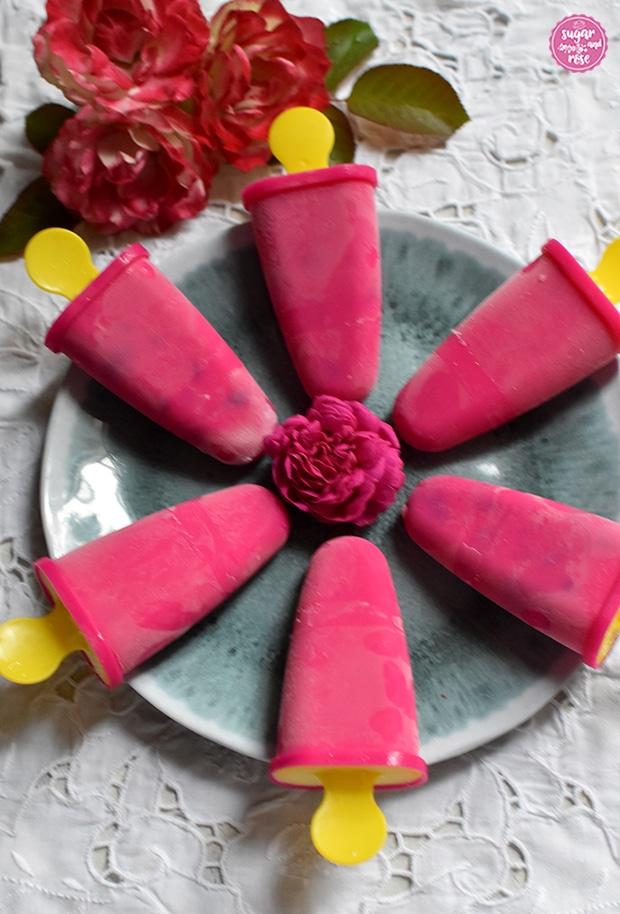Sechs pinkfarbene Eislutscherformen mit gelben Griffen liegen kreisförmig angeordnet auf einem taubenblau marmorierten Melaminteller, daneben zwei cremefarbene Rosenblüten mit roten Rändern (Blumenstadt Tulln)