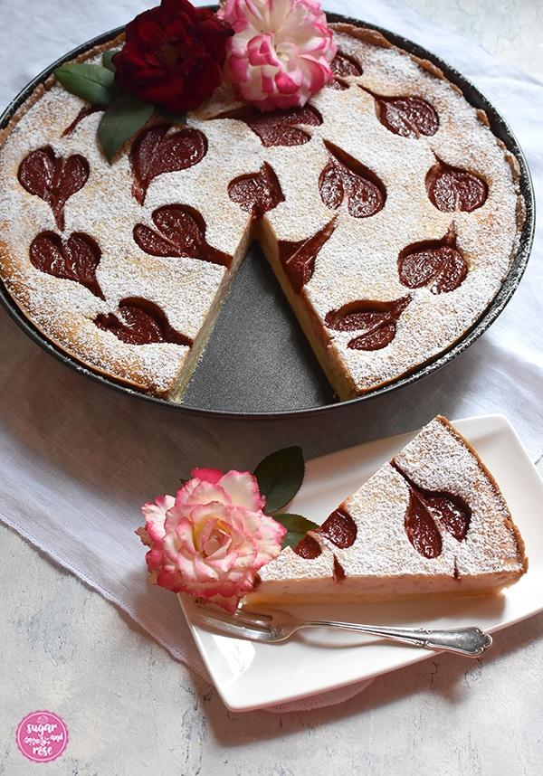Herzerl-Ricotta-Tarte mit Zwetschkenmus in einer runden Tarteform. Ein Stück Kuchen wurde herausgeschnitten und auf einem weißen rechteckigen Tellerchen mit Silbergabel präsentiert.