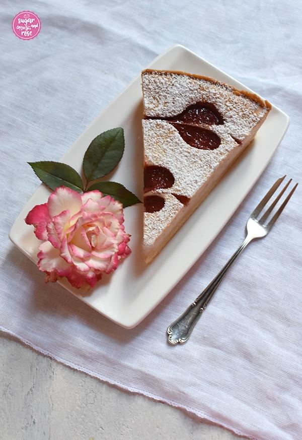 Ein Stück der Herzerl-Ricotta-Tarte mit Zwetschkenmus auf einem eckigen weißen Teller, dekoriert mit einer Rosenblüte (Blumenstadt Tulln, porzellanfarben mit roten Rändern) und grünen Rosenblättern. Daneben eine antike Silber-Dessertgabel auf einer weißen Leinenserviette