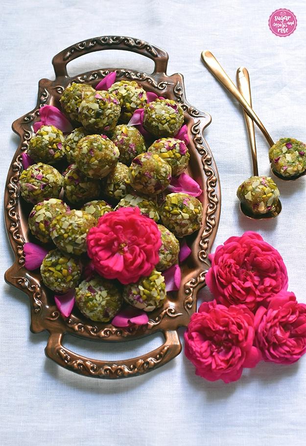Rosen-Safran-Energiekugeln auf kleinem Kupfertablett mir drei pinkfarbenen Rosen als Deko, daneben zwei kupferfarbene Löffel mit einem halbierten Energyball