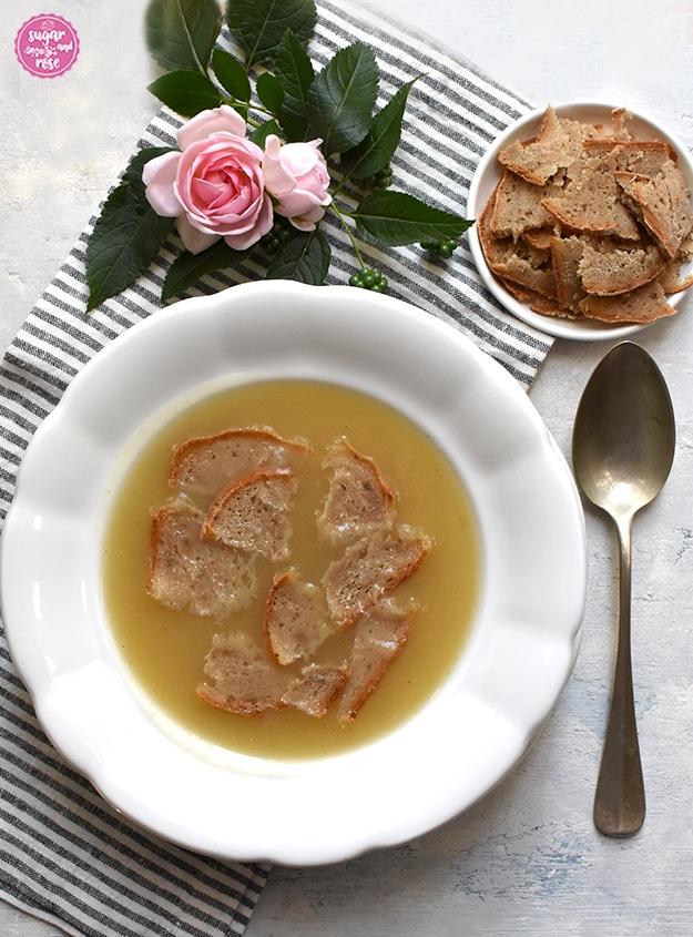 Weißer, alter Steinguteller mit Apfelkoch, daneben ein großer alter Suppenlöffel, dahinter ein kleines weißes Metallschälchen mit dünn aufgeschnittenen Brotschnitten, alles auf einer grau-weiß gestreiften Serviette mit rosa Rosenblüten und grünen Blättern dekoriert