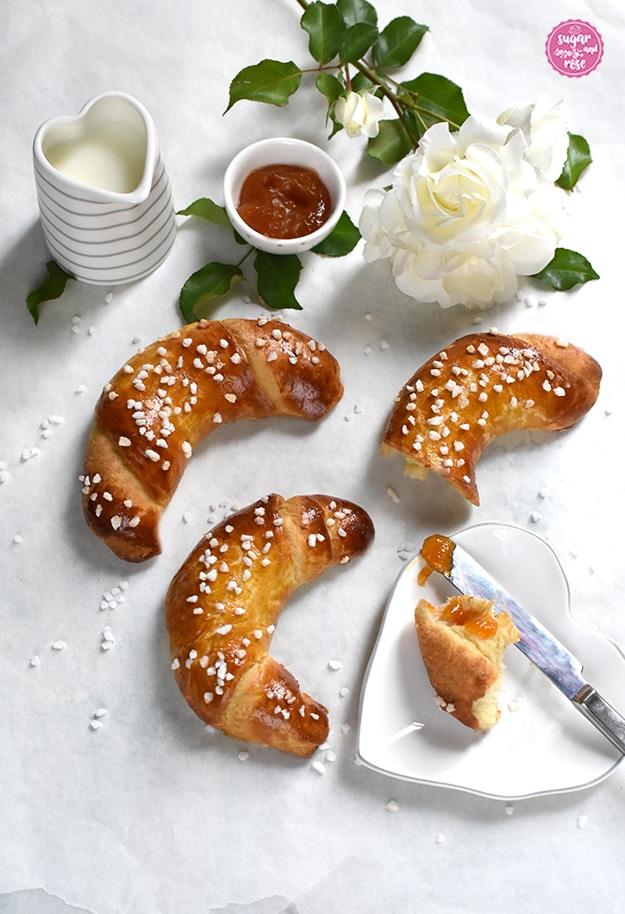 Zwei ganze und ein angebrochenes Briochekipferl auf weißer Tischplatte mit einer weißen Rose, daneben ein herzförmiges Milchkännchen und eine kleine Schale mit Marillenmarmelade sowie ein herzförmiger Teller mit einem Stück Brioche, ein Messer mit etwas Marmelade