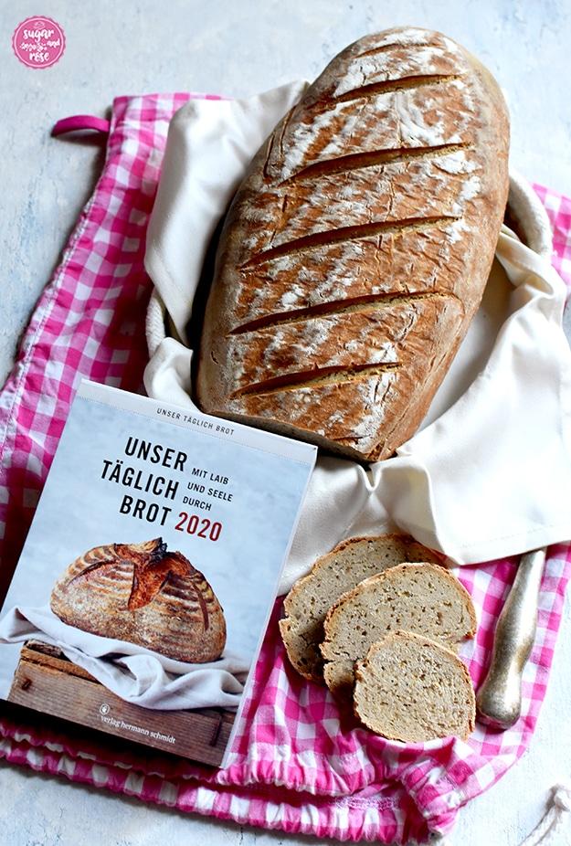 """Angeschnittenes Roggensauerteigbrot in Brotkörbchen mit weißer Stoffserviette, auf einem rosa-weiß karierten Brotsack, davor groß der Tagesabreisskalender """"Unser täglich Brot. Mit Laib und Seele durch 2020"""", ein altes Brotmesser und einige Scheiben vom Brot"""