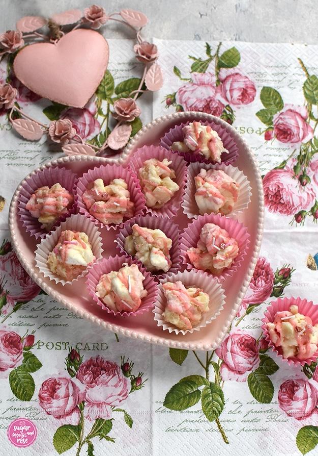 Rocky Road Konfekt in rosa und weißen Pralinenförmchen in einer rosa Keramikherzschale auf einer Serviette mit Rosenmotiven