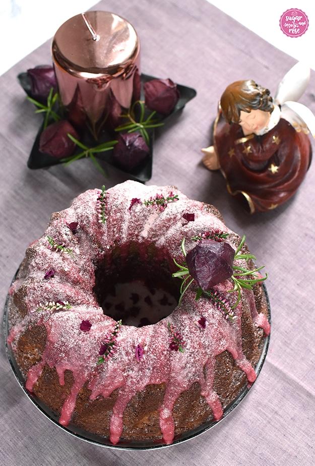 Punschgugelhupf mit rosa Zuckerguss auf Leinenserviette, dahinter ein sitzender, schlafender Porzellanengel und eine rosegoldene Kerze auf einem Sternenteller