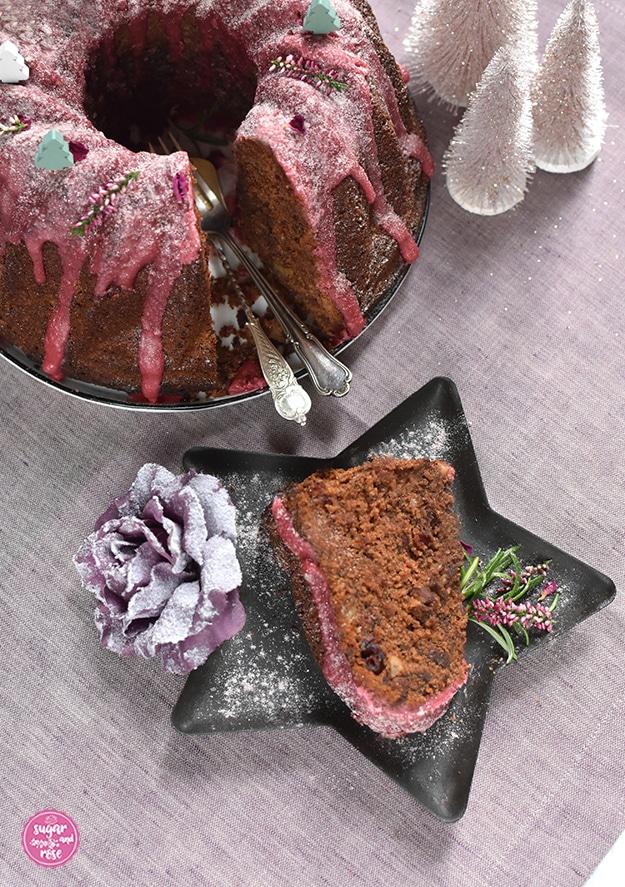 Ein Stück Punschgugelhupf mit Schokostückchen, Nüssen und Cranberryeinschlüssen auf ein einem Sternenteller, daneben Rosmarin und Erikablüten, dahinter der angeschnittene Gugelhupf mit Gabel und Löffel am Teller liegend