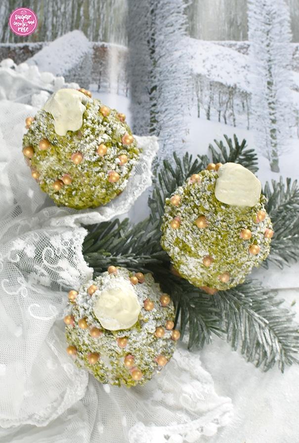 Drei süße Weihnachtsbäume zum Vernaschen mit Goldzuckerperlendeko auf einem beschneiten Tannenzweig, dahinter eine Zeitschrift mit verschneiter Winterlandschaft