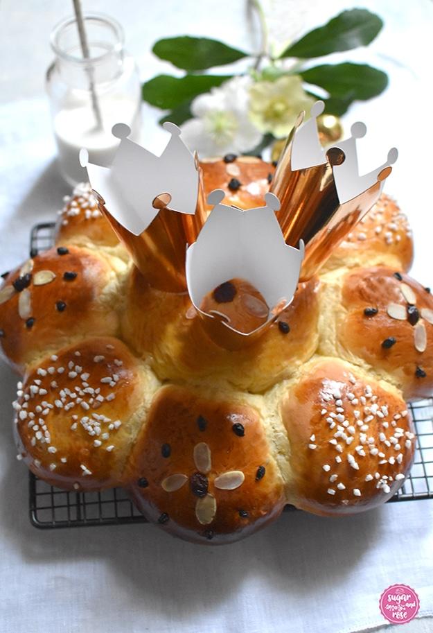 Dreikönigskuchen auf Gitterost, am Kuchen drei goldene Papierkrönchen, dahinter ein Glas Milch mit Strohhalm und Schneerosenblüten