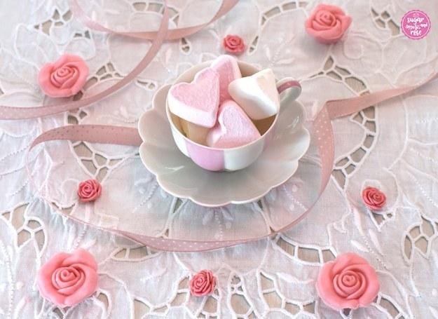 Augarten-Melone-Mokkatasse mit rosa Marshmallowherzen gefüllt auf weißem Lochstickerei-Tischset, dekoriert mit kleinen rosa Zuckerröschen und rosa Schleife
