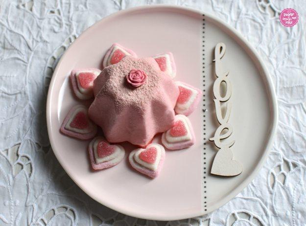 Weiß-rosa Keramikteller, darauf ein rosa Joghurttörtchen in Sternform, rundum das Törtchen liegen acht rosa-weiße Marshmallowherzen.