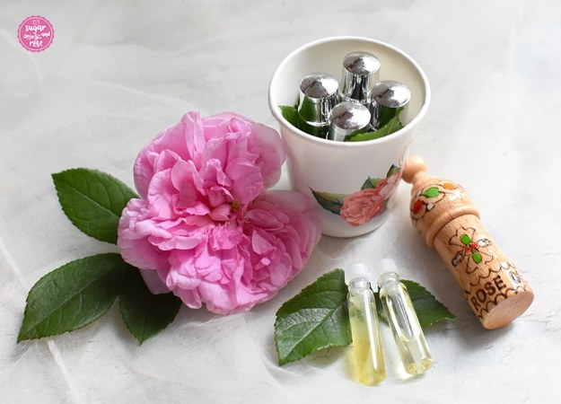 Rosenöl in Phiolen, vier in Metall, zwei in kleine Glas-Eprovetten, eine in Holz, daneben eine rosa Rosenblüte (Ispahan-Rose)