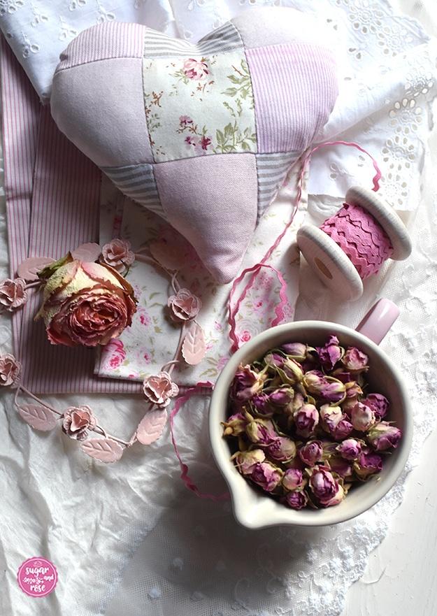 Rosenduftkissen in Herzform aus rosa-weiß gestreiftem, rosafarbenen und geblümten Stoffresten im Patchworkstil, davor eine Schale mit getrockneten Rosenblüten, Stoffreste und ein rosa Stoffband auf Spule