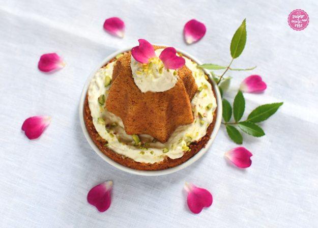 Ein sternförmiger Mini-Karottenkuchen auf einem kleinen weißen Metalltellerchen, dekoriert mit einem Klacks Frischkäsefrosting und zwei Rosenblüten, rundum verstreut pinkfarben Rosenblüten und grüne Rosenblätter