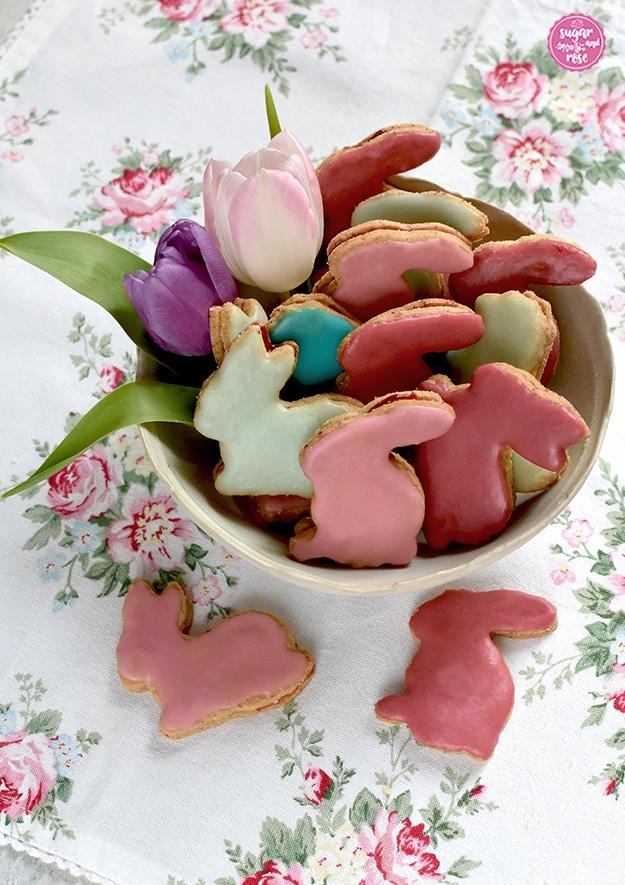 Osterhasen-Kekse in rosa, altrosa, mint und türkis in einer hellen Porzellanschale aufgeschichtet, dekoriert mit Tulpenblüten in flieder und hellrosa