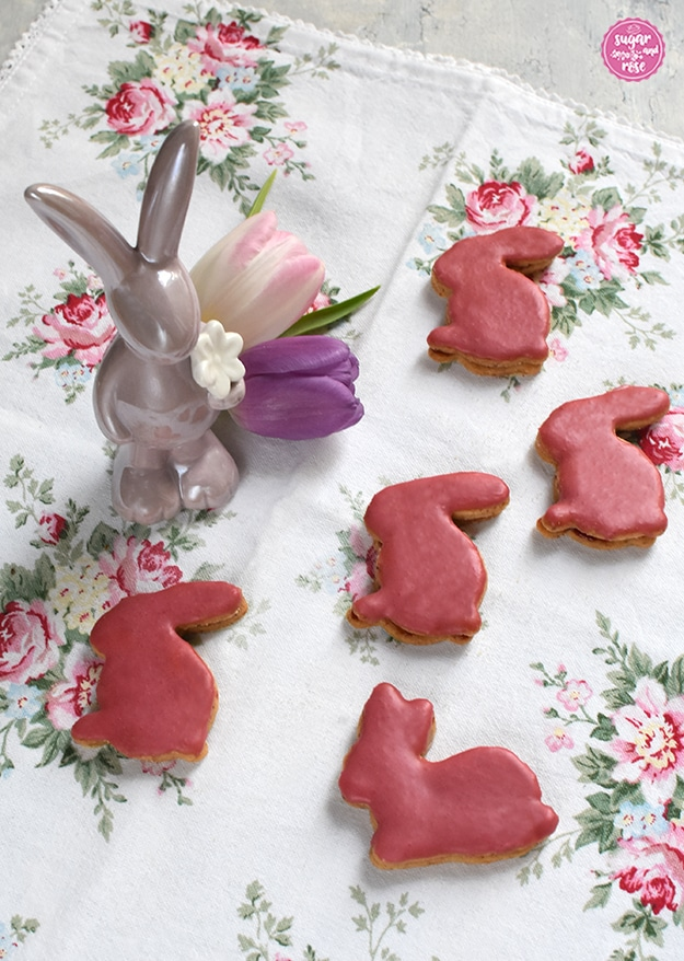 5 Osterhasen-Kekse in dunkelrosa glasiert auf einem Geschirrtuch mit Rosenblüten, dabei ein fliederfarbener Porzeallanhase und zwei Tulpen in rosa und flieder
