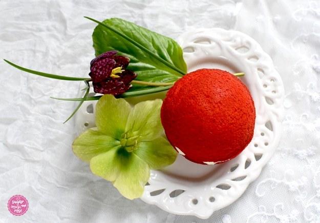 Ein herzförmiger weißer Keramikteller mit einem Whoopie und Blüten von der Schneerose und eine weinrote Schachbrettblume