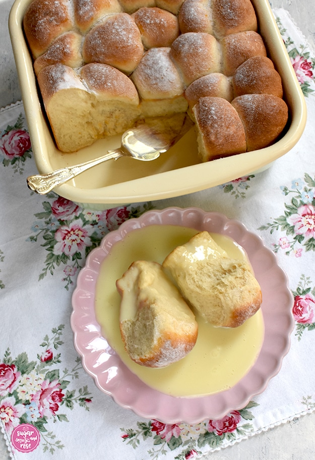 Marillenbuchteln in einer Riess-Pfanne auf Serviette mit Rosenmuster, einige Buchteln fehlen, dort liegt ein silberner Tortenheber. Davor ein rosa Keramikteller mit zwei Buchteln und Vanillesoße.