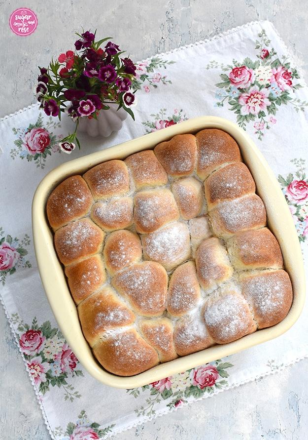Marillenbuchteln frisch gebacken und mit Staubzucker bestreut in einer Riess-Pfanne auf Serviette mit Rosenmuster, daneben eine kleine rosa Vase mit Bartnelken