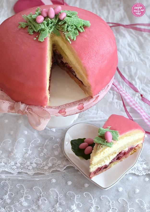 Rosa Ostertorte mit rosa und weißen Zuckereiern im Schokoosternest auf weißem Tortenständer, dekoriert mit rosa Schleife; ein Stück ist herausgeschnitten und liegt auf einem herzförmigen weißen Porzellanteller; hier sieht man die Himbeer-, Biskuit- und Vanillecremeschichten
