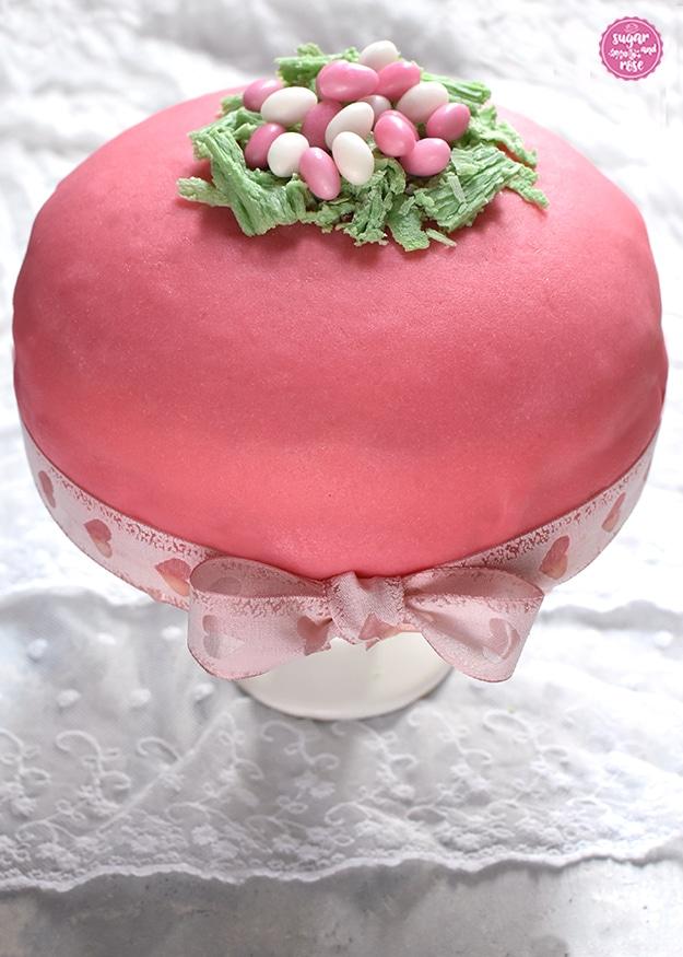 Rosa Ostertorte mit rosa und weißen Zuckereiern im Schokoosternest auf weißem Tortenständer, dekoriert mit rosa Schleife
