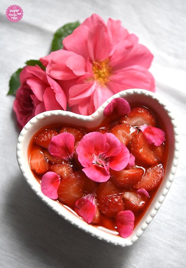 Ein herzförmige weiße Keramischale gefüllt mit Erdbeerkompott, dekoriert mit pinkfarbenen Geranienblüten, dahinter zwei pinkfarbene Rosenblüten