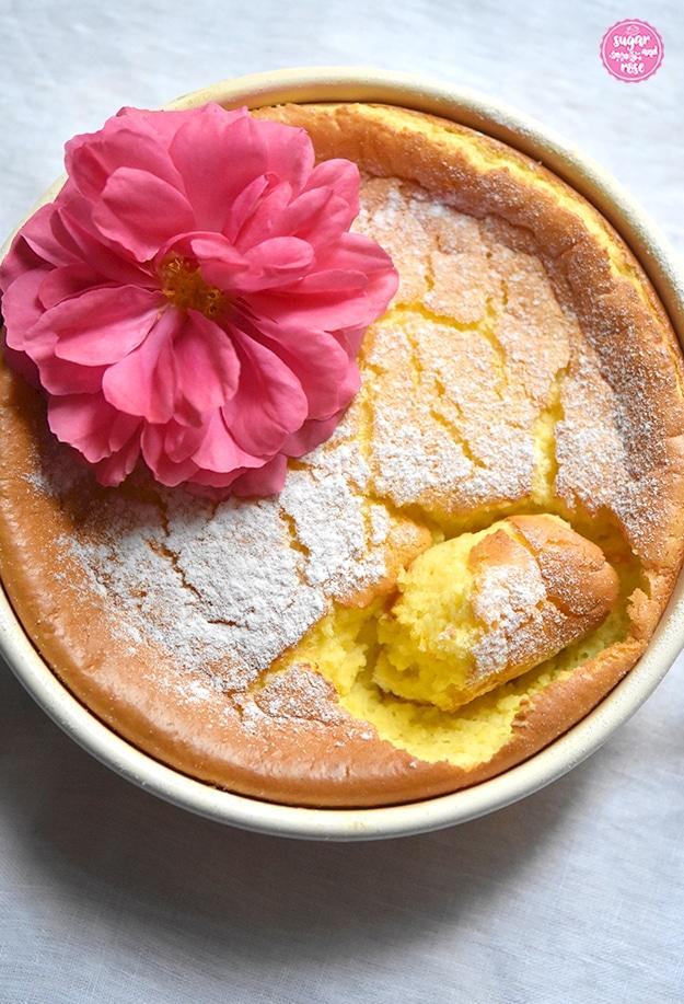 Grießauflauf in gelber Riess-Emailpfanne mit einer pinkfarbenen Rosenblüte dekoriert. Ein Stück vom Auflauf wurde bereits herausgestochen. Man sieht den safrangelben Auflauf innen.
